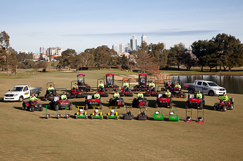 Variety of vehicles parked on public park space with workers showing Environmental Industries fleet.