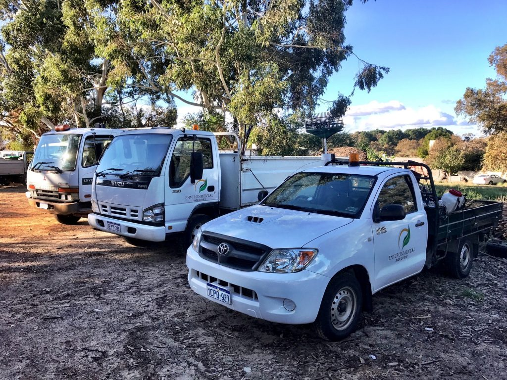 Three Environmental Industries fleet vehicles parked in a row.